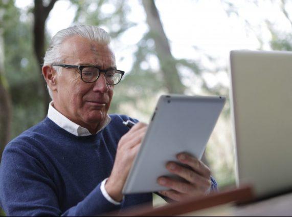 Man werkt op tablet en laptop